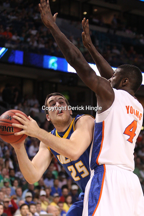 Mar 17, 2011; Tampa, FL, USA; UC Santa Barbara Gauchos forward Lucas Devenny (25) is defended by Florida Gators forward/center Patric Young (4) during second half of the second round of the 2011 NCAA men's basketball tournament at the St. Pete Times Forum. Florida defeated UCSB 79-51.  Mandatory Credit: Derick E. Hingle