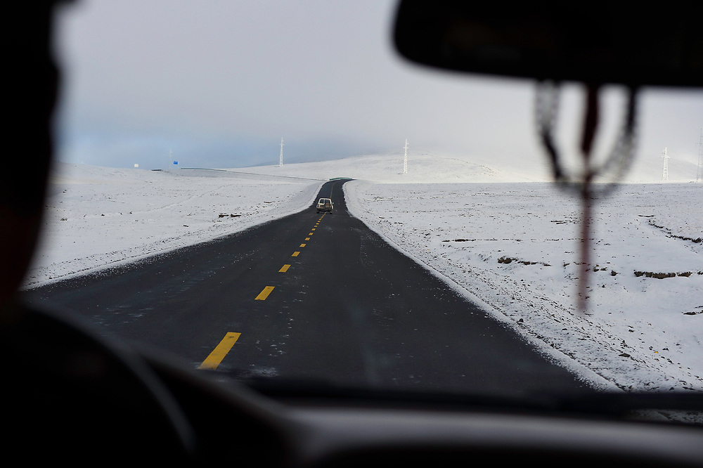 Driving through snow-clad hills of the Tibetan Plateau, Qumalai, Qinghai, China