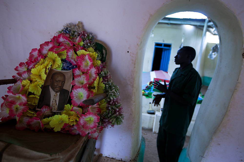 A soldier cleans up the shrine to the Nuba peoples greatest hero in the Nuba mountains.