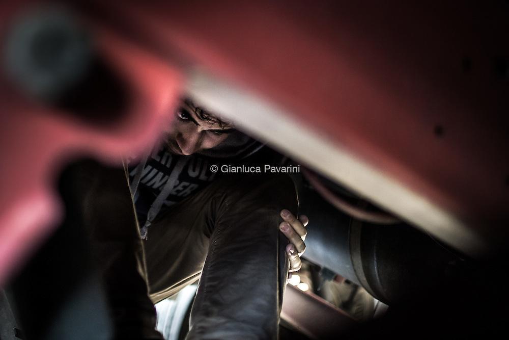 Un migrante si nasconde sotto ad un camion diretto a Londra. Calais (FR), all'imbarco dei traghetti per il regno unito, dopo il rafforzamento dei controlli, il numero di migranti cresce ogni giorno, nonostante i centri d'accoglienza siano stati amliati i migranti trovano riparo come possono all'interno di una foresta vicino alla strada che porta all'imbarco. In questo modo possono provare a nascondersi sui Camion, ma il numero sempre maggiore di persone sta creando una città parallela di gente senza identità.
