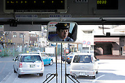 Japanese public bus driver seen in the rearview mirror