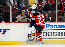 Nov 1, 2008; Newark, NJ, USA; New Jersey Devils defenseman Mike Mottau (27) hits Atlanta Thrashers right wing Colby Armstrong (20) during the first period at the Prudential Center.