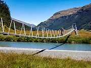 Crossing Rees River via swing bridge in Rees Valley Station on Rees-Dart Track, Otago region, South Island of New Zealand. In 5 days, we tramped the strenuous Rees-Dart Track for 39 miles plus 12.5 miles side trip to spectacular Cascade Saddle, in Mount Aspiring National Park.