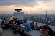 State Tower. Customers of Distil Bar enjoy a splendid sunset panoramic of Bangkok.