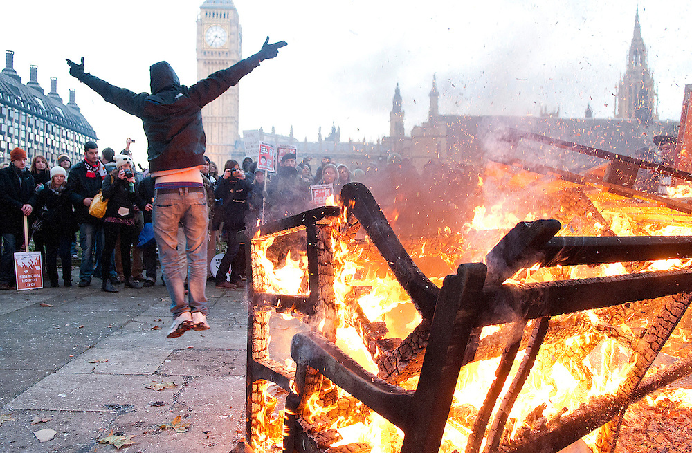 A hooded student protesting against a rise university tuition fees celebrates after adding wood to the fire in Parliament Square, London.