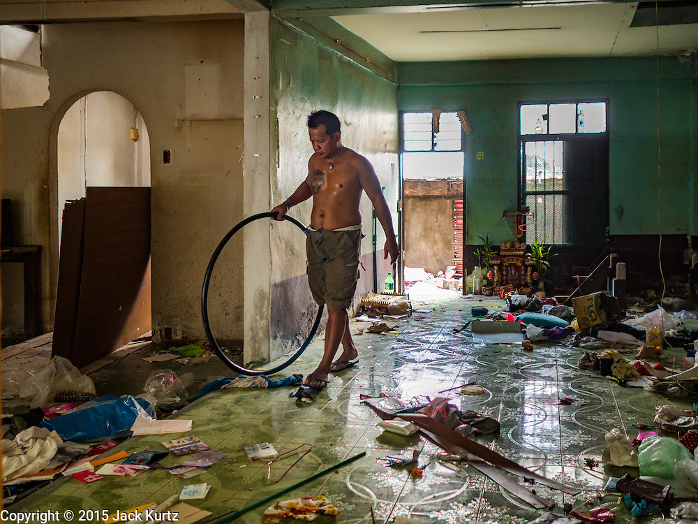 16 NOVEMBER 2015 - BANGKOK, THAILAND:  A scavenger walks through an abandoned home in the Wat Kalayanamit neighborhood. Fifty-four homes around Wat Kalayanamit, a historic Buddhist temple on the Chao Phraya River in the Thonburi section of Bangkok, are being razed and the residents evicted to make way for new development at the temple. The abbot of the temple said he was evicting the residents, who have lived on the temple grounds for generations, because their homes are unsafe and because he wants to improve the temple grounds. The evictions are a part of a Bangkok trend, especially along the Chao Phraya River and BTS light rail lines. Low income people are being evicted from their long time homes to make way for urban renewal.          PHOTO BY JACK KURTZ