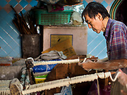 "29 DECEMBER 2018 - BANGKOK, THAILAND: A man makes longevity noodles in his family shophouse. The family has been making traditional ""mee sua"" noodles, also called ""longevity noodles"" for three generations in their home in central Bangkok. They use a recipe brought to Thailand from China. Longevity noodles are thought to contribute to a long and healthy life and  are served on special occasions, especially Chinese New Year, which is February 4, 2019. These noodles were being made for Chinese New Year.     PHOTO BY JACK KURTZ"