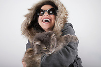Woman wearing hooded coat holding cat laughing