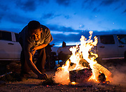 Frank Martinez, a member of the Tohono O'odham Nation, stokes a fire used for prayer outside of a meeting in Sells, Ariz. to discuss President Trump's plan to build a border wall on February 17, 2017. The U.S.-Mexico border runs through the reservation and tribal leaders have denounced plans to build the wall. (For The New York Times)