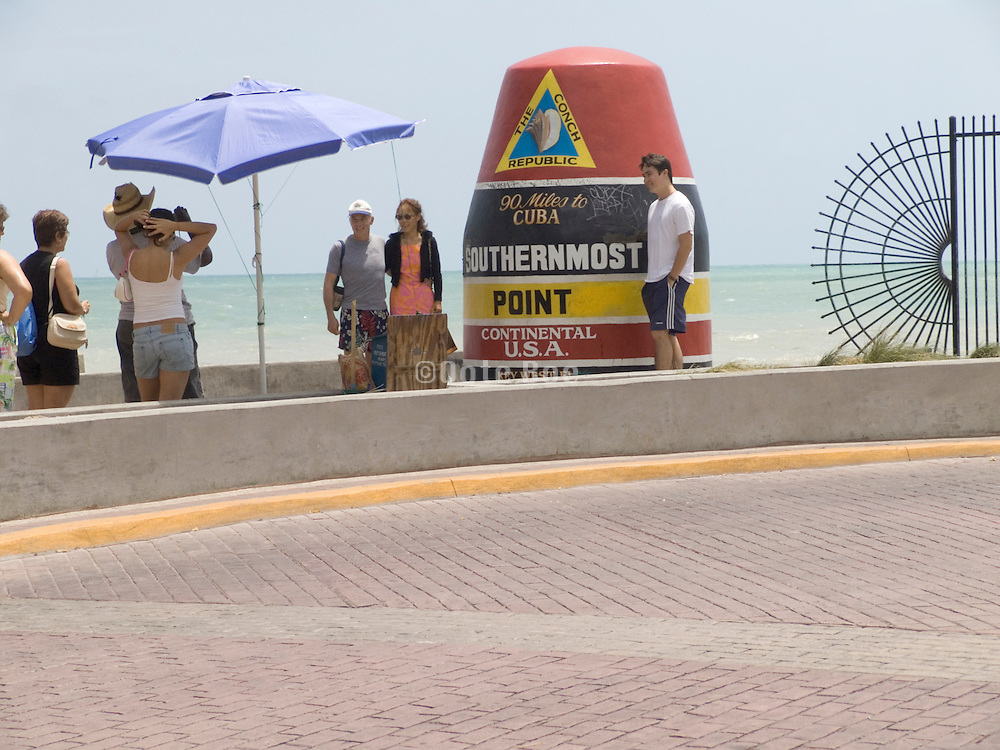 Tourists taking snapshots at the southernmost point marker Key West USA