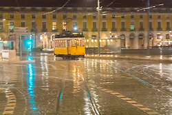 An iconic yellow tram of Lisbon makes its way through the rain-slick streets