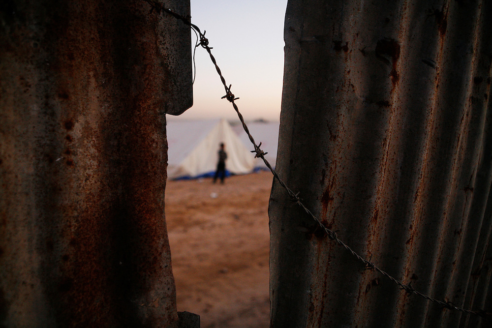 In the midst of their ongoing siege of the Gaza Strip, on 27 December Israel launched attacks by air, land and sea against the 1.5 million Palestinians of Gaza. The attacks, said to put an end to homemade rocket fire from armed groups in Gaza into Israel, left more than 1,300 Palestinians killed, the majority of whom were civilians including almost 450 children. Thousands of homes and businesses were also destroyed throughout the territory.///A young boy stands outside tents setup for the thousands of homeless people whose homes were destroyed in the Ezbat Abed Rabu neighborhood of Jabaliya in the Gaza Strip.