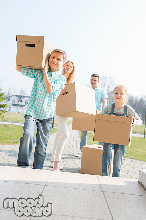 Family carrying cardboard boxes while entering new house