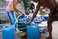 A woman sells water to urban slum dwellers as they queue their water buckets and cans up in Paranaque, Metro Manila, The Philippines on 19 January 2013. Photo by Suzanne Lee for Save the Children UK
