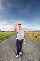 Full length portrait of young man making stop gesture at country road