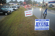 A man walks past campaign signs as voters go to the polls in the rain at the National Guard Armory in Oxford, Miss. on Tuesday, November 2, 2010.