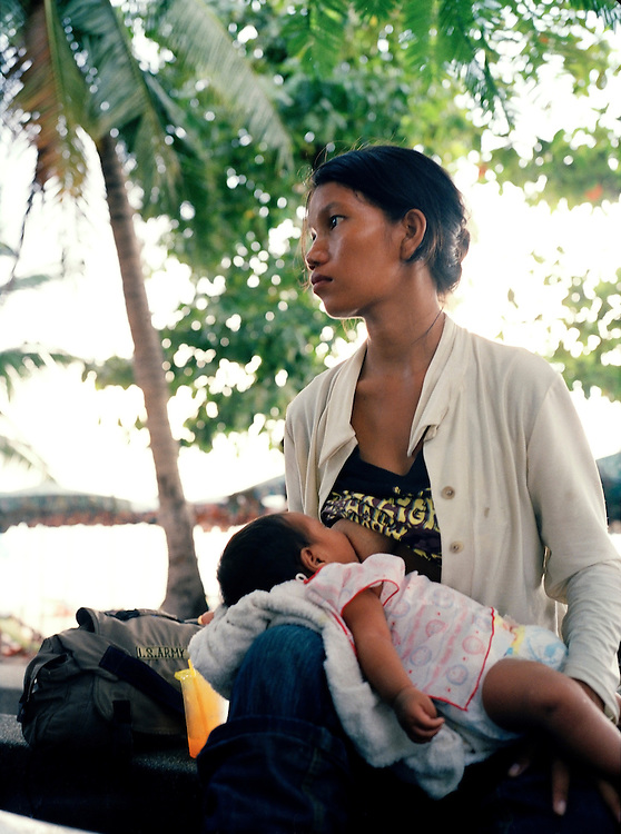 A mother breast feeds her child on Pattaya's beach promenade.