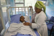 Young African boy, Mlekeleli, age 4, had a serious head trauma when the roof of his house collapsed during a storm.  His mother, by his side, is adjusting his tracheotomy.  He is receiving palliative care at  Clairwood Hospital, Durban, South Africa provided by Bigshoes Foundation.
