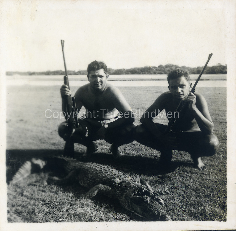 """The croc hunters are Dr Lance Fernando (with the telescopic sight on his rifle) & Shirley Andrado. Date is Nov 53 at Bagura & the croc was in the lagoon or actually basking on the bank. The rifle is a .270 Winchester."""