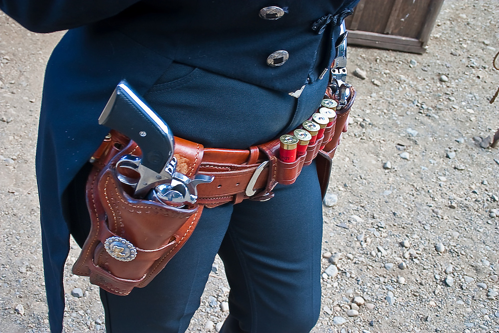 Cowgirl standing with pistol and cartridge loaded belt, ready for action