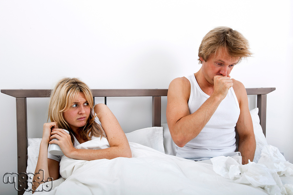 Scared woman looking at man coughing in bed