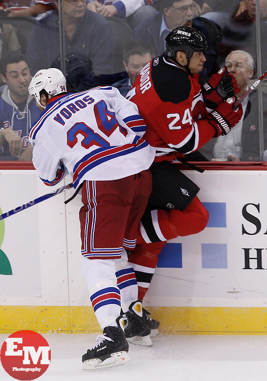 Oct 5, 2009; Newark, NJ, USA; New York Rangers center Aaron Voros (34) hits New Jersey Devils defenseman Bryce Salvador (24) during the second period at the Prudential Center.