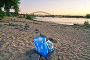 Nederland, Nijmegen, 8-7-2018 Warme zomerse dag op het Waalstrand van Nijmegen in de Ooijpolder, makkelijk te bereiken via de voetgangersbrug Ooijblik die hier ligt. Het zwemmen in de rivier de waal, rijn, is gevaarlijk vanwege de veraderlijke stroming en de drukke scheepvaart. Veel mensen maken een wandeling door de ooijpolder . Wilde paarden, koniks, lopen langs het water . Er is een kleine nevengeul gegraven met een voetgangersbruggetje eroverheen zodat het gebied nog meer natuurwaarde heeft gekregen . een groot probleem is het afval wat achtergelaten wordt. ook al zit het in tassen, de wilde dieren die hier rondlopen gaan erin snuffelen en kunnen ziek worden . De inhoud wordt meestal zwerfvuil wat later in de rivier belandt . Plastic, plastc soup, soep .Foto: Flip Franssen