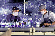 CDC Bebidas Plastic Bottling plant in Cochabamba Bolivia. Two factory workers wearing face masks whilst working on one of the assembly lines. <br /> <br /> Tel 0044(0)208 944 6933<br /> www.linkphotographers.com Photography by Orde Eliason