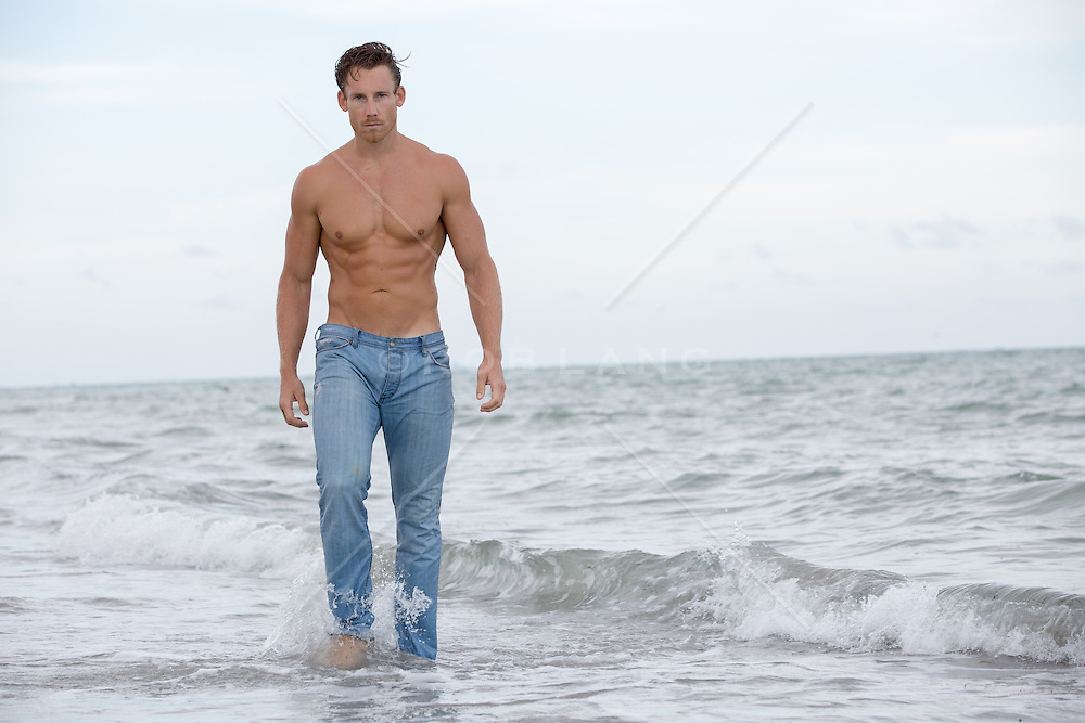 hot man in wet jeans walking in the ocean