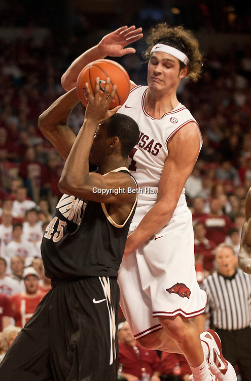 Jan 29, 2012; Fayetteville, AR, USA; Arkansas Razorbacks forward Michael Sanchez (31) attempts to block a shot made by Vanderbilt Commodores forward Rod Odom (45) during the first half of a game at Bud Walton Arena. Mandatory Credit: Beth Hall-US PRESSWIRE