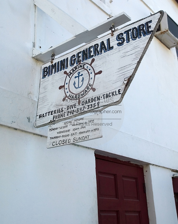 Sign for Bimini general store along the King's Highway in Alice Town on the tiny Caribbean island of Bimini, Bahamas. Golf carts are the main form of transportation on the island.