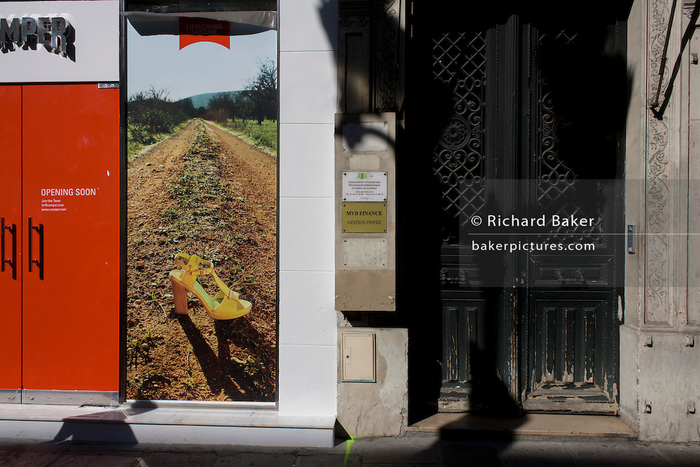 Old French doorway and new ad announcing a new retail shop for shoemaker Camper in Rue de Rivoli, Paris.