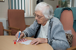 People enjoy socialising and activity at a council run over 50's club in Basildon, Essex. Women enjoying their weekly bingo game. *Model Released*