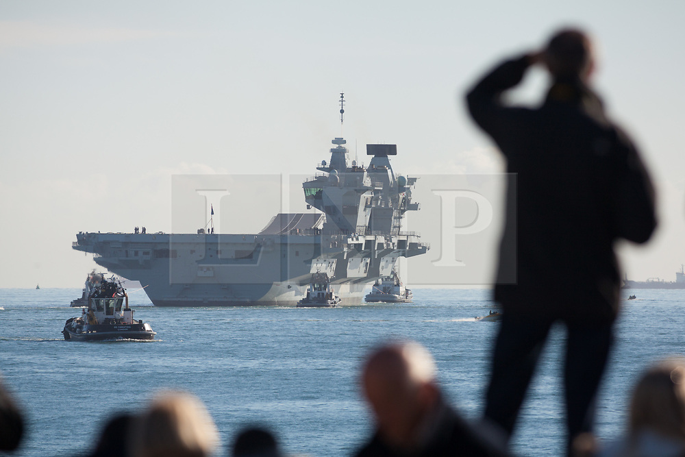 © Licensed to London News Pictures. 30/10/2017. Portsmouth, UK.  A man watches as people gather to watch the Royal Navy's flagship, HMS Queen Elizabeth, as she departs Her Majesty's Naval Base (HMNB) Portsmouth for the first time since her arrival on 16/08/2017.  The new aircraft carrier is heading back to sea for the second stages of her sea trials.<br /> <br /> Flight trials involving the new F-35B Joint Strike Fighter are expected to take place off the coast of the U.S. next year, and she is due to come into service in the early 2020s.  Photo credit: Rob Arnold/LNP
