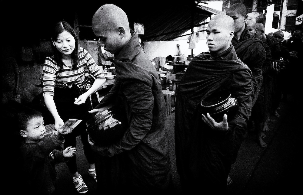 Monks receiving alms on the streets of Yangon (Rangoon) Myanmar (Burma) January 2012