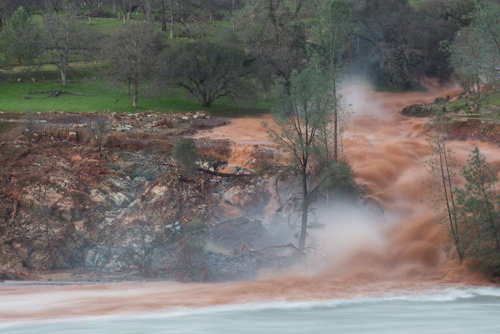 Turbid water that spilled over the Oroville dam emergency spillway, used for the first time in the dam's history, flows into the feather river.  February 11, 2017.