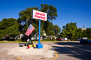 "03 AUGUST 2020 - JEWELL, IOWA:  RUSTY HOCKMAN cleans up the front of the Jewell Market before the store's reopening Monday. Hockman's family used to own the grocery store. The only grocery store in Jewell, a small community in central Iowa, closed in 2019. It served four communities within a 20 mile radius of Jewell. Some of the town's residents created a cooperative to reopen the store. They sold shares to the co-op and  held fundraisers through the spring. Organizers raised about $225,000 and bought the store, which had its ""soft opening"" July 8. The store celebrated its official reopening Monday August 3. Before the reopening, Jewell had been a ""food desert"" for seven months. The USDA defines rural food deserts as having at least 500 people in a census tract living 10 miles from a large grocery store or supermarket. There is a convenience store in Jewell, but it sells mostly heavily processed, unhealthy snack foods that are high in fat, sugar, and salt.           PHOTO BY JACK KURTZ"
