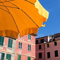 Italy, La Spezie, Sidewalk cafe's umbrella in Cinque Terre village of Vernazza along Mediterranean Coast on spring afternoon.