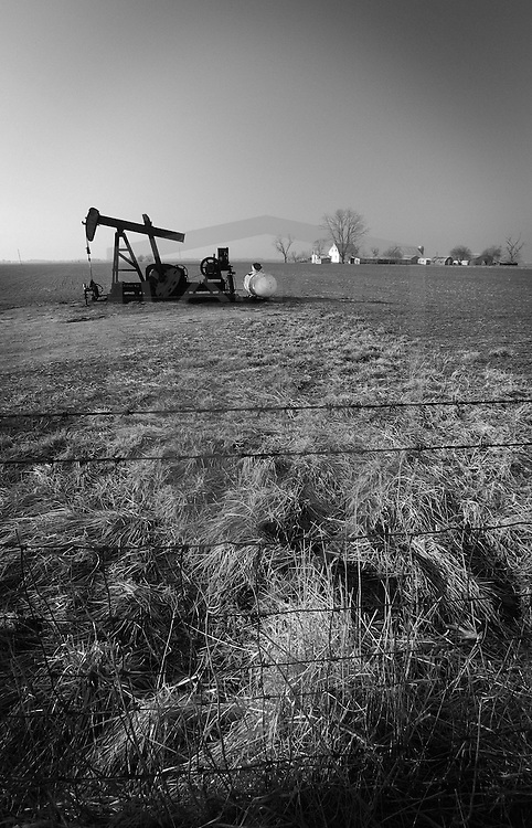 indiana rural oil rig meadow and distant farmhouse, black and white, vertical, copy space