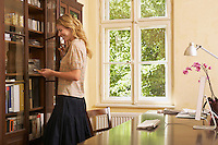 Young woman looking in cabinet in living room