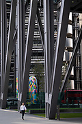 "An office worker walks beneath the architecture of  22 Leadenhall Street, (aka the Leadenhall Building) on Leadenhall Street in the City of London during the Coronavirus pandemic, a time when office workers are still largely still working from home, on 16th September 2020, in London, England. The commercial skyscraper opened in July 2014 and was designed by Rogers Stirk Harbour + Partners and is informally known as ""The Cheesegrater"" because of its distinctive wedge shape."