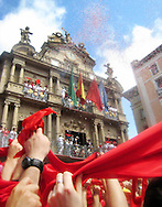 "People wave the traditional red scarves in front of the Pamplona Town Hall, as they celebrate the ""Chupinazo"", the fireworks with whose explosion the San Fermin festivities start, on July 6, 2008, in Pamplona, north of Spain. A man jumps from the Navarreria fountain to fall on the crowd celebrating the ""Chupinazo"", the fireworks with whose explosion the San Fermin festivities start, on July 6, 2008, in Pamplona, north of Spain."