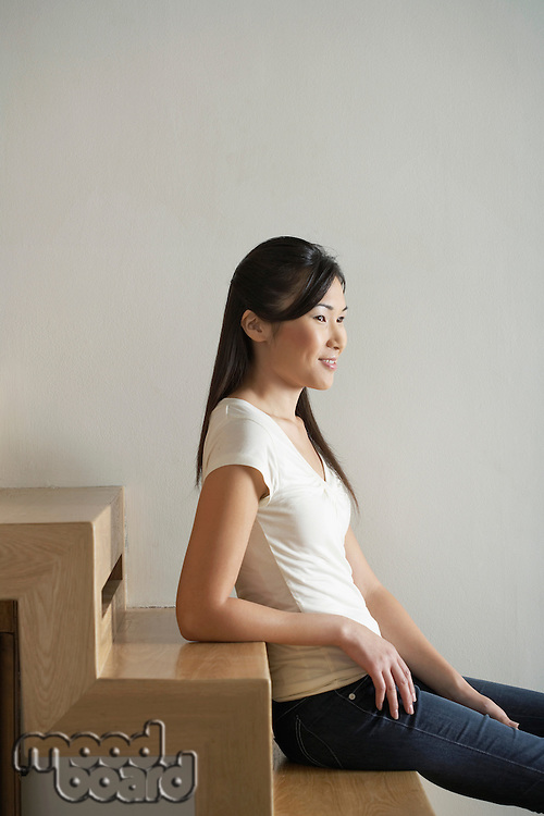 Young Woman Sitting on wooden staircase side view