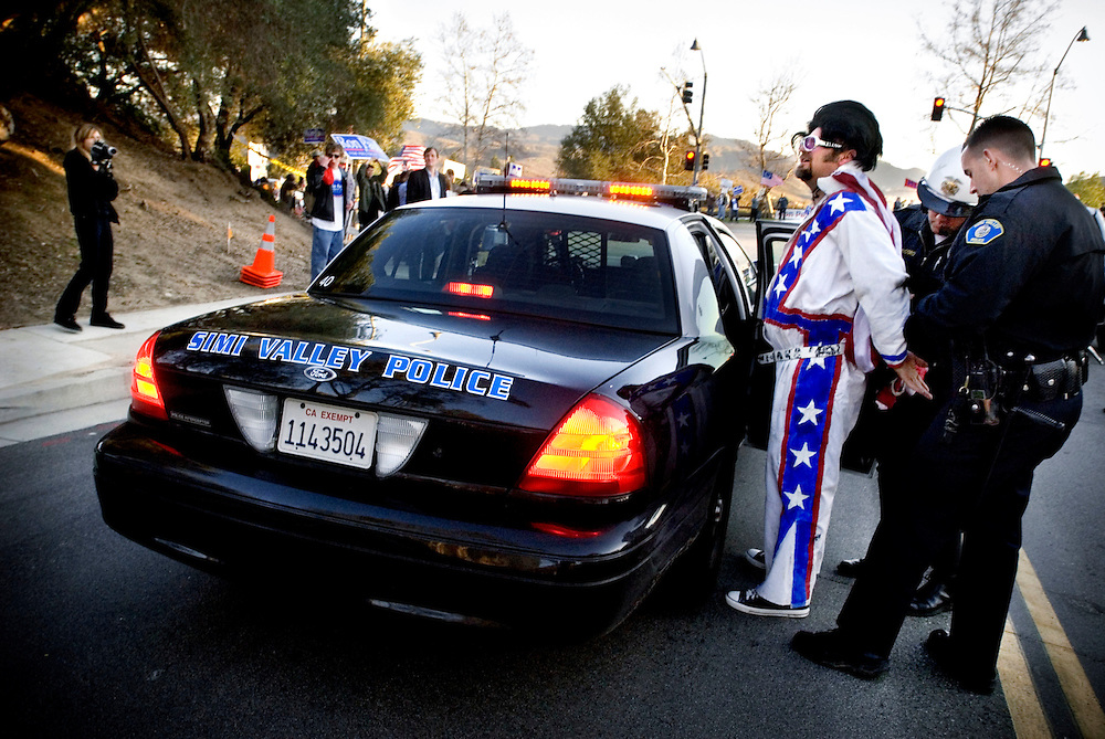 """Republican debate at Ronald Reagan Presidential Library in Simi Valley, California. A Ron Paul supporter dressed as Elvis is arrested after jaywalking. Other supporters scream """"Free Elvis"""" as police officers handcuff him...Photographer Chris Maluszynski /MOMENT"""