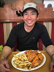 Wildlife photojournalist Noppadol Paothong enjoys his tradition of eating a plate of chicken wings after spending the morning photographing grouse. (Editor's note: See before and after photos). ©John L. Dengler / DenglerImages.com