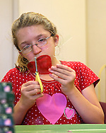 Cassie Koehn, 13, of Elgin, works on cutting out her shrinky dinks craft during a summer camp hosted by the Iowa School for the Deaf at the Iowa Braille and Sight Saving School in Vinton on Tuesday, July 16, 2013.