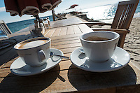 Two cups of coffee sit on a brown wooden slatted table on the beach at Juan-les-Pins on the French Riviera.<br />