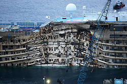 60490198<br /> Isola del Giglio, Italy. <br /> A view of the wreck of Italy's Costa Concordia cruise ship after it emerged from the water on September 17, 2013, near the harbour of Giglio Porto. On 13 January 2012, she was wrecked off the coast of Isola del Giglio in Italy. She has been declared a total loss and is being salvaged as of 2013, following which she will be scrapped, Italy, Tuesday September 17, 2013,<br /> Picture by imago / i-Images<br /> UK ONLY