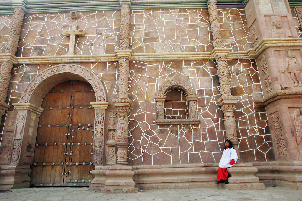 "A girl sits in front of a church that Father Sebastian Obermaier built in El Alto, Bolivia. a town he has lived in for 27 years .  ""I don't feel Bolivian, I feel Aymara"" he says, referring to the Aymara indigenous population that makes up more than 80% of El Alto. Father Obermaier has been designing and building churches in El Alto for the past 10 years, with a goal of building one church for every 10,000 inhabitants of the city, which currently has nearly 700,000 people living in it.  Everyone that visits Bolivia can see his numerous churches from the window of their airplane as it lands in El Alto.  The churches are marked by a style unique to Father Obermaier, that mixes indigenous symbols with tall towers and bright colors, that leave every church looking different, as if they were straight out of a children's pop-up book."