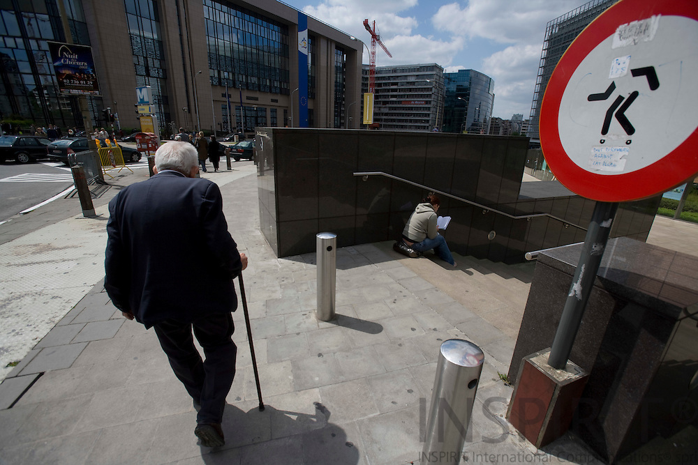 BRUSSELS - BELGIUM - 19 MAY 2008 -- An old retired man supported by his walking stick at the round point Schuman between the European Council and Commission. A young woman sits at the stairs reading a book. Photo: Erik Luntang